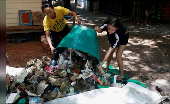 Thailand's former national windsurfer Amara Wichthong and her daughter collect rubbish near Pattaya beach at Chonburi, Thailand on May 12. [REUTERS/YONHAP]