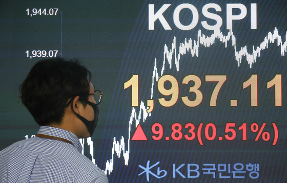 A dealer walks past an electronic signboard in the dealing room of KB Kookmin Bank in Yeouido, western Seoul, Monday. The Kospi closed at 1,937.11, a 9.83 point rise from the previous close. [YONHAP]