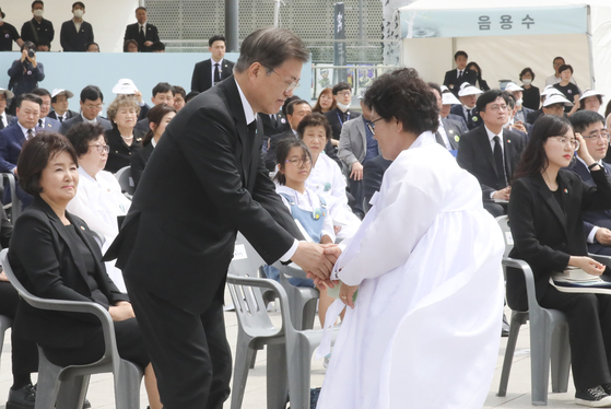 President Moon Jae-in, left, greets a victim's relative at acommemoration ceremony to mark the 40th anniversary of May 18, 1980 Gwangju Democratization Movement on Monday.  [YONHAP]