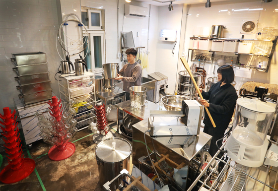 The brewers of Guruma Brewery working in their kitchen in Mapo District.