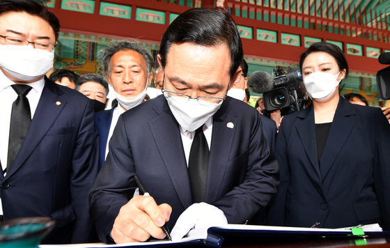 Rep. Joo Ho-young, floor leader and acting head of the United Future Party, signs a guestbook at the May 18 National Cemetery on Monday.  [YONHAP]