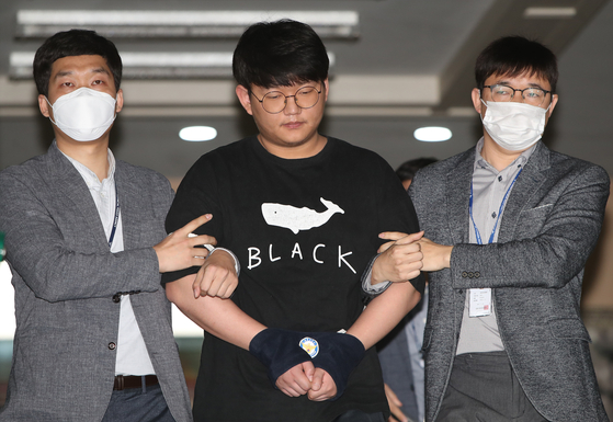 Moon Hyung-wook, the suspected operator of one of the earliest online sex trafficking rings on Telegram, is led out by police for a perp walk in front of the press at the Andong Police Precinct on Monday. [YONHAP]