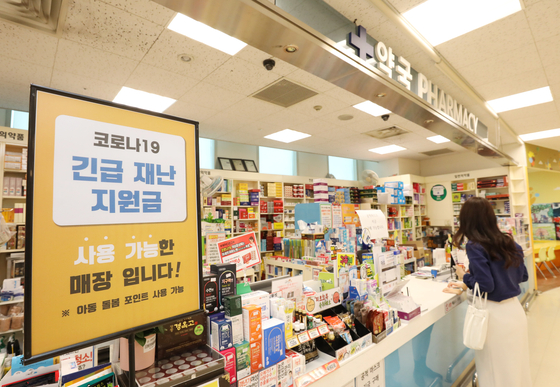A sign at a drug store in Emart inSeongsu-dong, eastern Seoul, indicates that it accepts the emergency disasterrelief funds. [EMART]