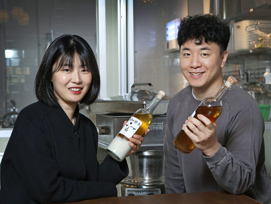 The two entrepreneurs behind Guruma Brewery, Yang Yoo-mi, left, and Lee Du-jae, show off their drink Meeting Point that they made together. [PARK SANG-MOON]