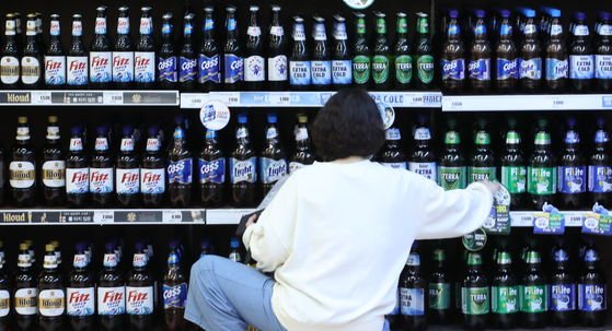 Beers displayed at a major store in downtown Seoul on Tuesday. The government — the Ministry of Economy and Finance and the National Tax Service — announced an easing of alcoholic drink regulations, which includes allowing manufacturers and retailers to sell alcoholic beverages through delivery services. Additionally, alcoholic beverages can be purchased via smartphone. There will no longer be a different label for those sold to ordinary customers to those sold to businesses such as restaurants and bars. Beer and traditional makgeolli makers are no longer required to report to the government when making changes to prices. Smaller alcoholic beverage manufacturers will be permitted to outsource their production to other companies to reduce their capital costs. The easing of regulations was introduced in order to help boost the competitiveness of the Korean alcoholic beverage industry, which has recently been losing ground to imported competition. [YONHAP]