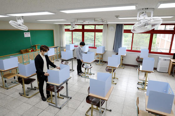 Teachers at Junghwa Girls' High School in Daegu set up shields on each desk Tuesday, a day before classes for high school seniors begin for the first time since the coronavirus outbreak. [NEWS1]