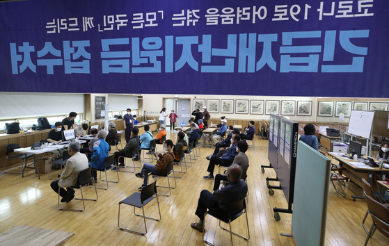 Residents of Seoul wait in a community center to apply for emergency relief grants Monday. [YONHAP]
