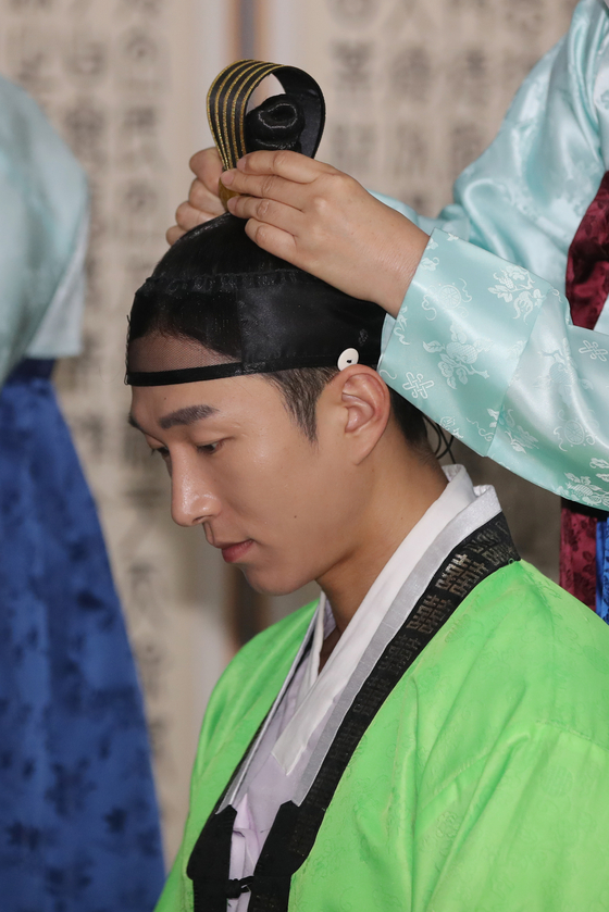 A man has his hair tied up in a topknot during a traditional coming-of-age ceremony held at the Gwangju Hyanggyo, a state-owned Confucianism school in Gwangju, Wednesday. [YONHAP]
