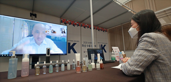 """An employee of a cosmetics company is having a teleconference with a potential buyer abroad, Wednesday, at the 'Brand K"""" event held in Coex, Samseong-dong in southern Seoul. The Ministry of SMEs and Startups have partnered with relevant government bodies to support exports. [YONHAP]"""