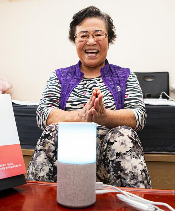 A woman in her 60s listens to SK Telecom AI speaker Nugu. [SK TELECOM]