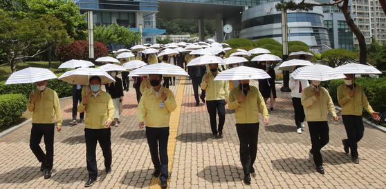 Officials from Nam District Office in Busan on Thursday promote a Carrying a Parasol campaign to keep social distance in daily life and cool off in the soon-to-come summerheat. [SONG BONG-GEUN]