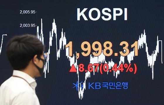 A dealer walks past an electronic signboard in the dealing room of KB Kookmin Bank in Yeouido, western Seoul, Thursday. [YONHAP]