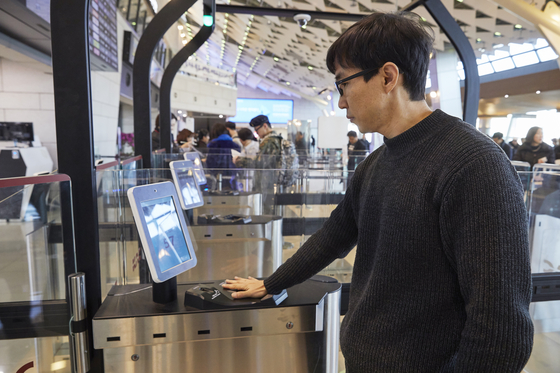 A passenger uses the palm vein authentication system at Gimpo International Airport on Monday. [KWAK JAE-MIN]