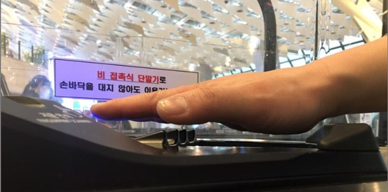 A passenger puts his hand over the palm vein authentication system to enter the departure gate. [KWAK JAE-MIN]