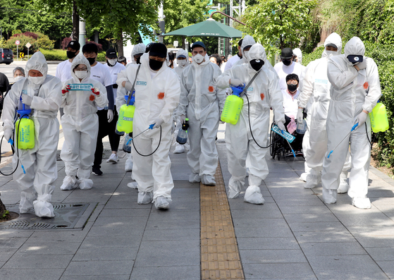 Business owners in Itaewon-dong, central Seoul, spray disinfectant on the streets of Itaewon Wednesday as a cluster of infections linked to the area's nightclubs and bars continues to swell. [NEWS1]