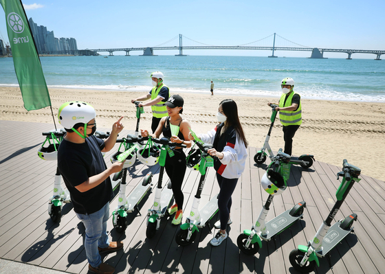 A safety instructor from electric scooter-sharing service Lime is educating riders on safety rules Thursday at the Gwangalli Beach in Busan. The revision to the traffic law passed on Wednesday stipulates that from November riders of electric scooters can use bike lanes. Helmets will be required and riders must be at least 13 years of age. [LIME KOREA]