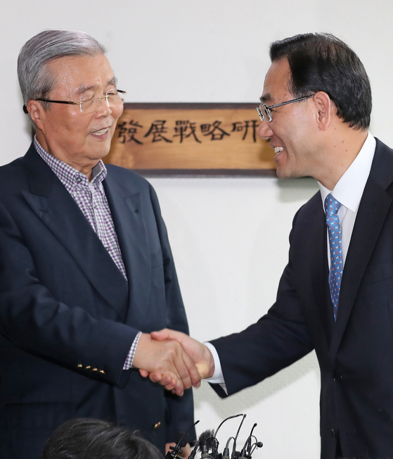 Kim Chong-in, left, shakes hand with Rep. Joo Ho-young, floor leader of the United Future Party, on Friday. They agreed that Kim will head the party as interim leader until April next year.