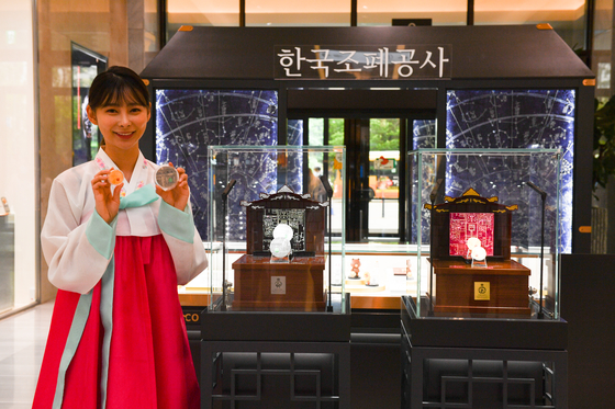 Medallions made with designs inspired by Gyeongbok Palace are on display at Hyundai Department Store's Pangyo branch in Gyeonggi. A portion of the proceeds will be donated to help state-run agencies to acquire and preserve Korean heritage found overseas. [Komsco]