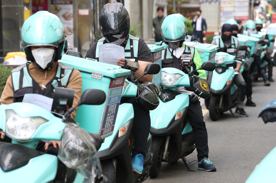Baedal Minjok (Baemin) food delivery riders in Yeouido,western Seoul, on May 1. The acquisition of Baemin to Germany's Delivery Hero has again raised concern over the online platform's dominance. [YONHAP]