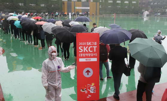 Applicants for jobs at SK Group are told to keep a distance from one another on Sunday while queuing up to enter a building at Seokyeong University in Seongbuk District, northern Seoul, to take a written test. [NEWS1]