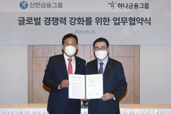 Hana Financial Group Chairman Kim Jung-tae, left and Shinhan Financial Group Chairman Cho Yong-byoung sign an MOU on Monday on joint global expansion in central Seoul. [SHINHAN FINANCIAL GROUP]