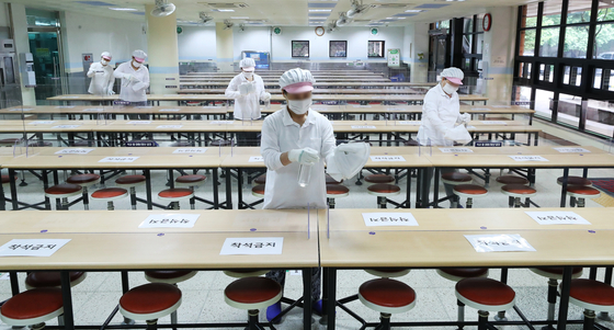 Employees disinfect tables and partitions at the cafeteria of Maeyeoul Elementary School in Suwon, Gyeonggi, on Monday, two days before the school opens for first and second graders. [YONHAP]
