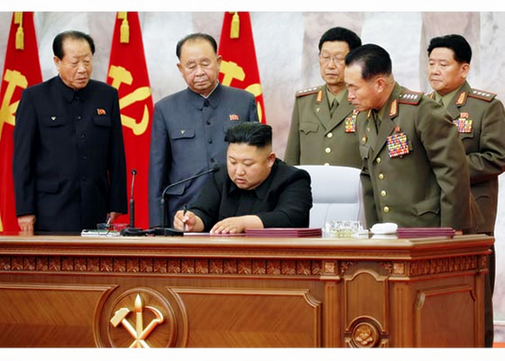 North Korean leader Kim Jong-un signs an order at a meeting of the ruling Workers' Party's Central Military Commission, with recently promoted military officials looking on, in a picture carried in Pyongyang's official Rodong Sinmun Sunday. [YONHAP]