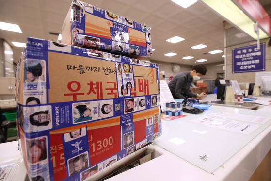 A delivery box is wrapped with Hope Tape at Gwanghwamun Post Office in central Seoul on Monday to mark International Missing Children's Day. Hope Tape, available for customers to use as packaging tape at 22 general post offices in Seoul, is covered with descriptions of missing children. [YONHAP]