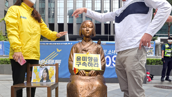 "A statue symbolizing victims of Japanese wartime sexual slavery in Jongno District, central Seoul, on Monday is seen with a sign calling for the imprisonment of lawmaker-elect Yoon Mee-hyang, who has been questioned over her financial transparency by Lee Yong-soo, a ""comfort woman"" survivor. Two youth groups clashed over the placement of the sign that day. [YONHAP]"