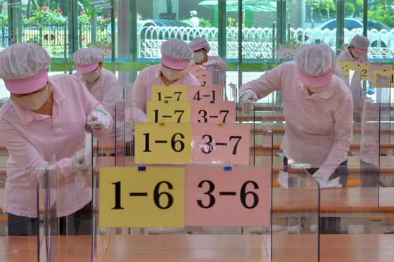 Cafeteria workers at Jigok Elementary School in Pohang, North Gyeongsang, wipe tables and plexiglass dividers Tuesday, a day before first and second graders return to school for the first time since the Covid-19 pandemic. [NEWS1]