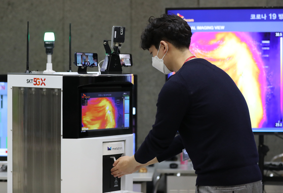 An employee disinfects his hand using an autonomous disinfectant robot deployed at SK Telecom's headquarters in Euljiro, Jung District, in central Seoul on Tuesday. SK Telecom announced Tuesday that it has co-developed the robot with industrial automation solution provider Omron that can monitor and send visitor data via the 5G network to a central server. [YONHAP]