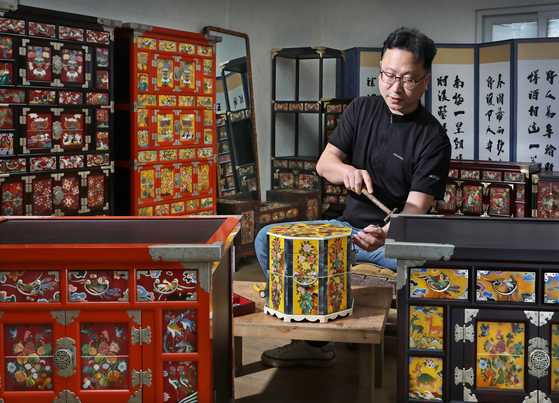 Han Ki-ho works on hwagak crafts at his studio located in Icheon, Gyeonggi. Hwagak is a traditional decorative technique using ox horns. He learned the technique from his father Han Chun-seop (1949-2015), who was a master artisan in hwagak. [PARK SANG-MOON]
