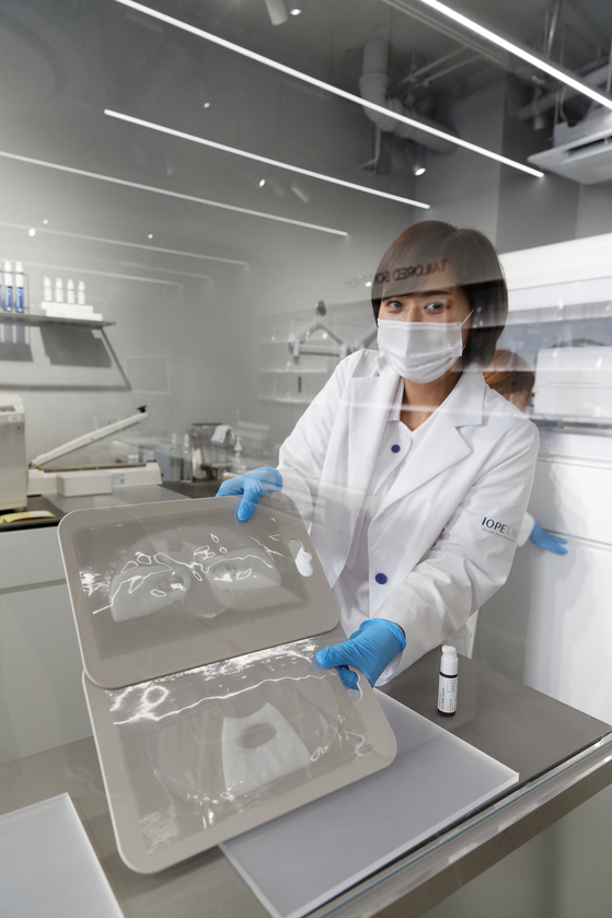 An Iope Lab employee holds up the 3-D printed sheet masks. [AMOREPACIFIC]