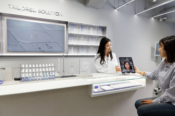 A customer at Iope Lab in Myeong-dong, central Seoul, sits for a photo to have her facial structure measured for a 3-D printed sheet mask. [AMOREPACIFIC]