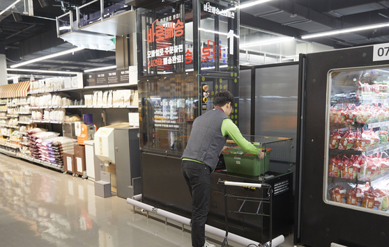 A Lotte Mart employee at the Gwanggyo branch in Suwon, Gyeonggi, prepares an order placed online. [LOTTE SHOPPING]
