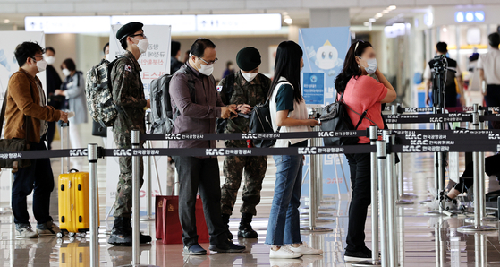 Passengers at Incheon International Airport queue up to board a flight while wearing masks Tuesday, a day before the Korean government's order requiring all air travelers to wear face coverings goes into effect. [NEWS1]