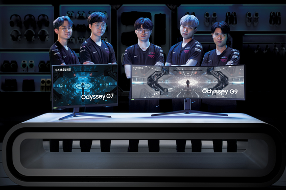 T1's League of Legends team, including three-time world champion Faker, center, stands behind Samsung Electronics' gaming monitors Odyssey G7, left, and G9. [SAMSUNG ELECTRONICS]