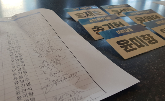 Yoon Mee-hyang's badge, bottom at the left row, is left uncollected at the Democratic Party's meeting of its lawmakers-elect.  [YONHAP]