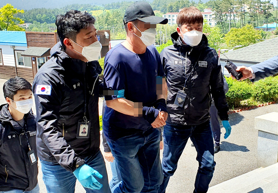 Police escort a Chinese man apprehended Wednesday who is accused of sneaking into Korea on a motorboat with six others last week. [YONHAP]