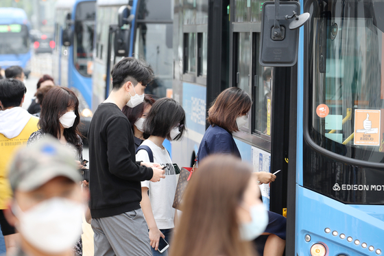 People are seen wearing face masks as they board a bus in Seocho District, southern Seoul, Monday, a day before a new rule goes into effect that allows bus and taxi drivers to refuse passengers without a face covering. [YONHAP]