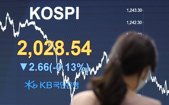 An employee looks at the benchmark Kospi index displayed on the screen attached to the walls of dealing room of KB Kookmin Bank, in the financial district of Yeouido, western Seoul, Thursday.