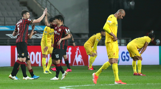 Gwangju FC players, in yellow, walk off the pitch after losing to FC Seoul 0-1 at Seoul World Cup Stadium on May 17. [YONHAP]