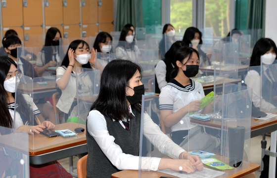 Seniors at Jeonmin High School in Daejeon sit at desks with plastic dividers on Wednesday. Schools reopened for the first time for high school seniors Wednesday since the coronavirus pandemic. [KIM SEONG-TAE]