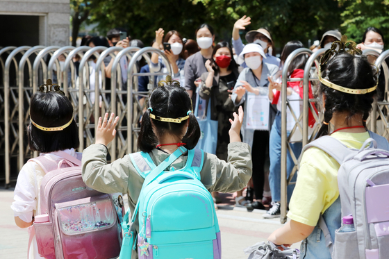 First graders at Maeyeoul Elementary School in Suwon, Gyeonggi, are greeted by their masked parents after their first day back to classes on Wednesday. The second batch of students, including kindergartners and first and second graders, returned to school for the first time Wednesday amid continued coronavirus concerns. [NEWS1]