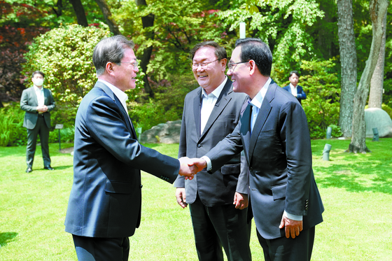 President Moon Jae-in, left, shakes hands with Rep. Joo Ho-young, floor leader of the main opposition United Future Party, right, before their luncheon meeting at the Blue House on Thursday. Rep. Kim Tae-nyeon, floor leader of the ruling Democratic Party, center, also attended the meeting. Moon invited the floor leaders on the eve of the start of the new National Assembly to seek bipartisan cooperation on state affairs amid the continuing coronavirus outbreak. The lawmakers elected last month to the 21st National Assembly will start their four-year terms on Saturday. [Blue House Press Corps]