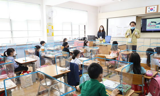 Students listen to their lesson behind plastic partitions at Seryun Elementary School in Songpa District, eastern Seoul, Wednesday. [YONHAP]