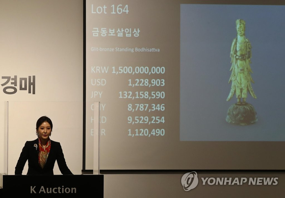 An auctioneer welcomes bids for Treasure No.285, Gilt-bronze Standing Bodhisattva, at K Auction in southern Seoul on Wednesday. [YONHAP]