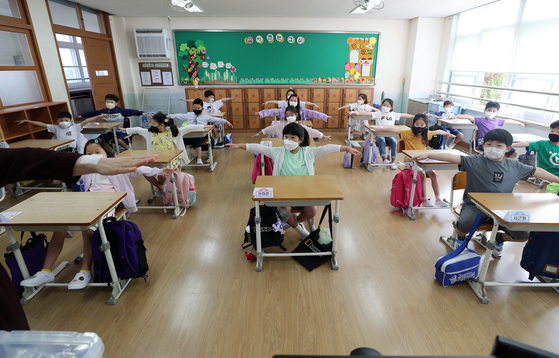 Students learn about social distancing on their first day back to in-person classes at Munhwa Elementary School in Daejeon Wednesday. [YONHAP]