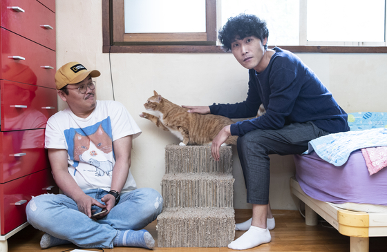"Producer Cho Eun-sung,left, and director Lee Hee-seop of the cat documentary ""Our Cats"" pose for a photo in Lee's home along with his cat and roommate, Lenny. [KWON HYUK-JAE]"