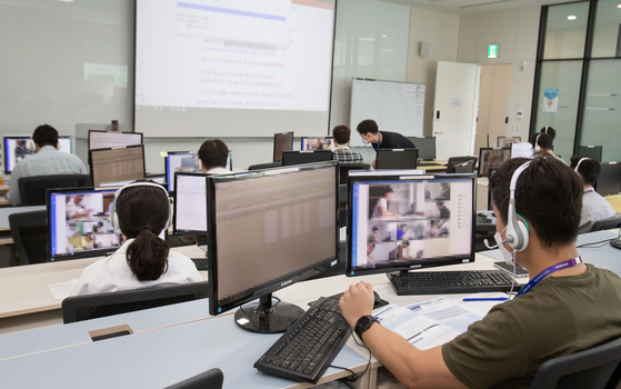 Inspectors keep an eye on takers of Samsung's annual recruitment test, the GSAT, in a control room inside the headquarters of Samsung Electronics in Hwaseong, Gyeonggi, Sunday. The company shifted its first round of written tests online due to the coronavirus outbreak. [YONHAP]